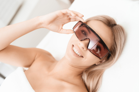 The woman came to the procedure of laser hair removal. Shes wearing red protective goggles.