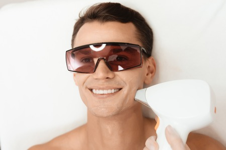 The doctor treats the face of a man with a modern laser epilator. The man lies and smiles. Banco de Imagens - 97781979