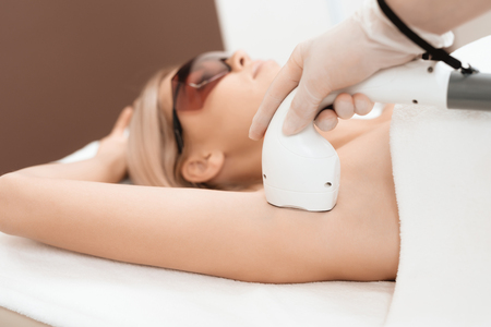 The woman came to the procedure of laser hair removal. The doctor treats her armpits with an apparatus.