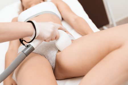 The woman came to the procedure of laser hair removal. The doctor is treating her leg with a device. Standard-Bild