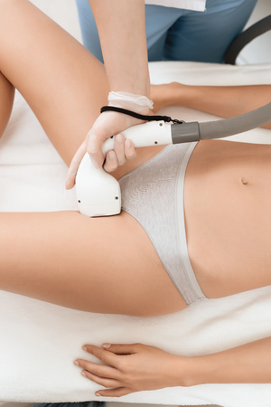 The woman came to the procedure of laser hair removal. The doctor processes her bikini area with the device.