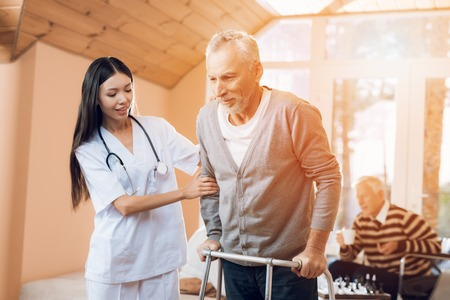 An asian nurse helps a man on an adult walker in a nursing home. Banque d'images