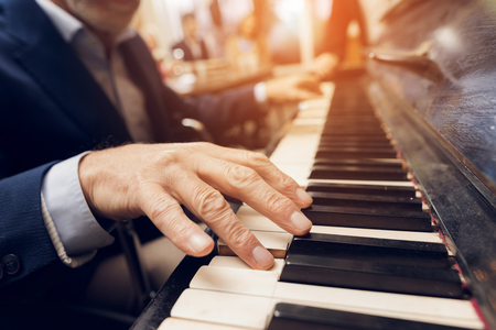 An elderly man plays the piano in a nursing home. Stock Photo