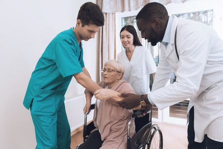 The nurse helps an elderly woman to get out of bed and get into a wheelchair.