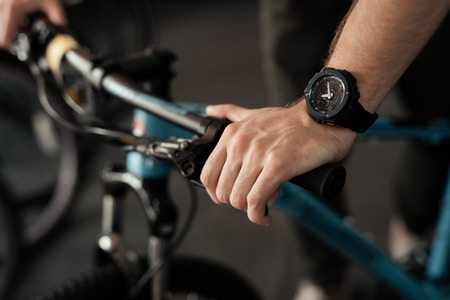 A young man holds the bicycle handlebars in the bicycle store. Stock Photo