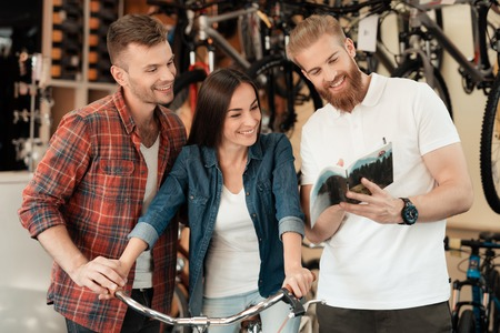 A young couple came to the bicycle shop to choose a new bicycle. Banco de Imagens