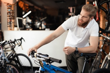 The seller in the bicycle shop holds the bicycle handlebars.