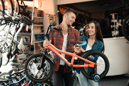 A young guy and a girl are choosing a childrens bicycle.