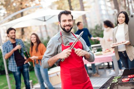 男はグリルで食べ物を調理しながら、カメラにポーズをとっています。 写真素材 - 91427684