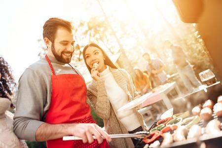 여자와 남자 바베 큐에 소시지와 야채를 튀김. 스톡 콘텐츠