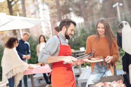 A guy and a girl are cooking barbecue food during a picnic with friends. Banco de Imagens - 91428646