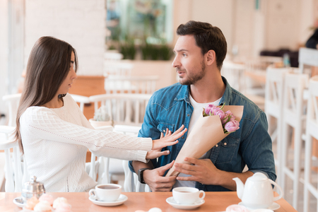 The girl refuses the flowers, which she gives a guy.