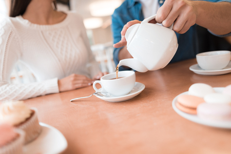 A guy and a girl are sitting together in a cafe. They drink tea, eat cakes. They are in love with each other. They are a couple.