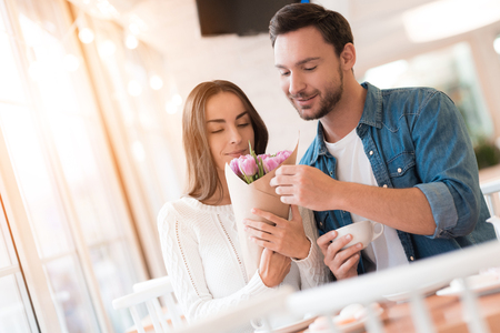 The guy gives flowers to the girl in the cafe.