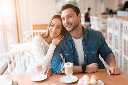 A guy and a girl are sitting together in a cafe.