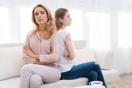 A woman and a girl are sitting on the sofa back to back.