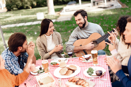 A man plays a guitar during a picnic with friends. Stock Photo