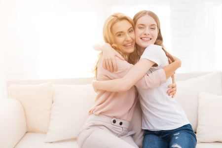Mom and teenage daughter embrace.