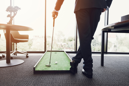 Close up. A man in a business suit playing golf in the office. He is playing on a green mat.