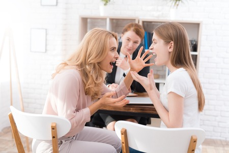 Mom and daughter-teenager at a reception with a psychologist. Stock Photo