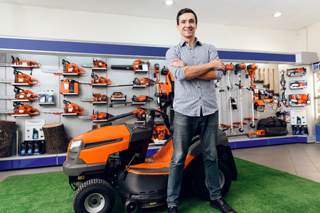 A man is standing near a lawn mower.