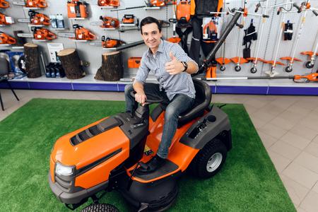 A man is sitting on a lawn mower.