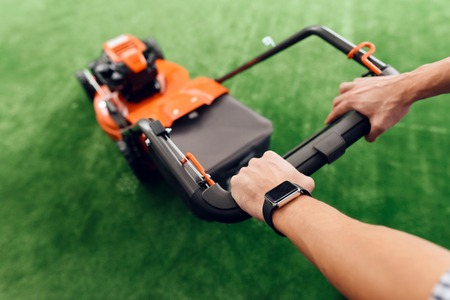 A man holds a lawn mower for the handle. He came to the tools store for gardening. He has a wristwatch on his hand. Banco de Imagens
