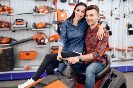 A young couple is sitting on a lawn mower. Standard-Bild