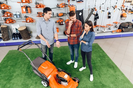 A consultant in a garden tools store shows a guy and a girl a lawn mower.