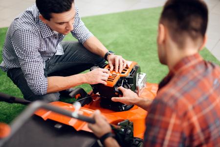 A man starts a lawn mower motor. Standard-Bild