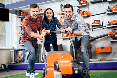 Three young people are posing with a lawn mower.