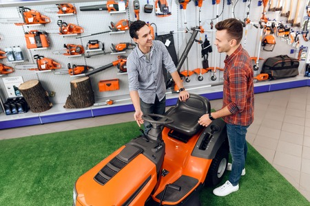 A consultant in a garden tools store shows a customer a lawn mower.