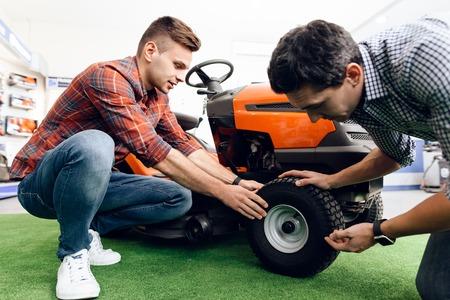 Um consultor em uma loja de ferramentas de jardinagem mostra ao cliente um cortador de grama. Foto de archivo - 91595678