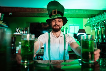 The barman is holding glasses with beer in his hands. Stock Photo