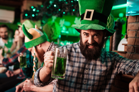 The guy in the cap of the leprechaun is drinking beer.