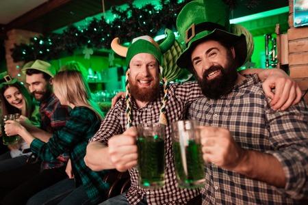 Two men in carnival caps celebrate St. Patricks Day.