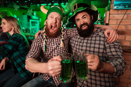Two men in carnival caps celebrate St. Patricks Day.