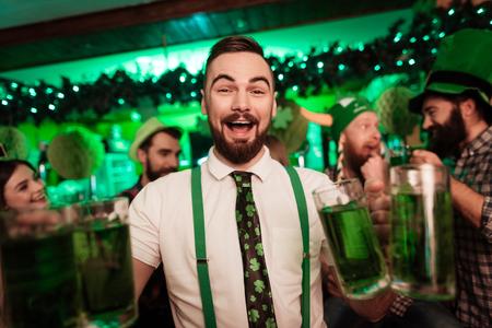 De barman houdt een bril met bier in zijn handen.