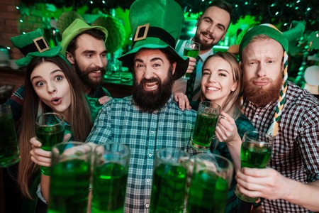 A company of young people posing on the camera with glasses of beer in their hands.