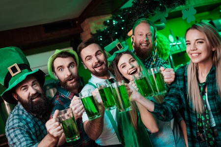 A company of young people is resting in a beer bar. Imagens