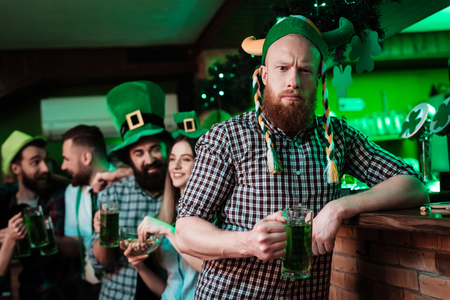 A man in a funny hat celebrates St. Patricks Day with friends.