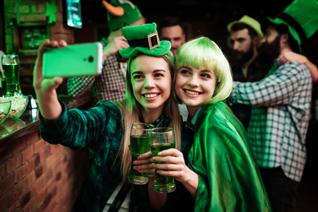 Two girls in a wig and hat make selfi at the bar. Stock Photo
