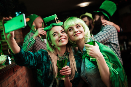 Two girls in a wig and hat make selfi at the bar. Archivio Fotografico