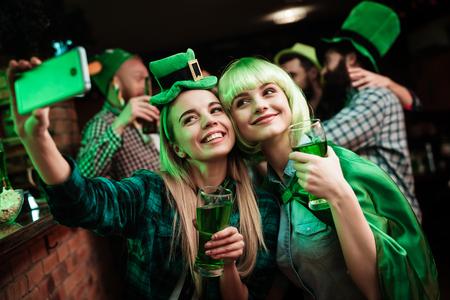 Twee meisjes in een pruik en hoed maken selfi aan de bar.