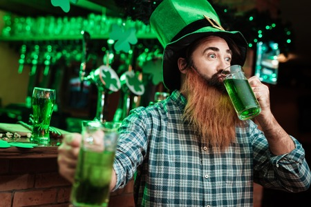 A man in a leprechaun hat and with a beard drinks beer in a bar.