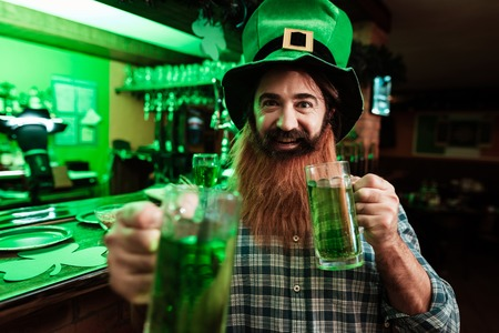 A man in a leprechaun hat and with a beard drinks beer in a bar. Banco de Imagens