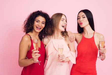 Three girls with champagne on pink background celebrating womens day March 8.