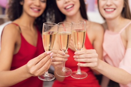 Three girls with champagne. They are celebrating womens day March 8.