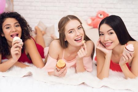 カップケーキを持ってベッドに横たわっている3人の女の子。彼らは3月8日の女性の日を祝っています。