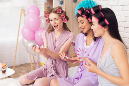 Three girls with curlers in their hair doing nail polish. They are celebrating womens day March 8.